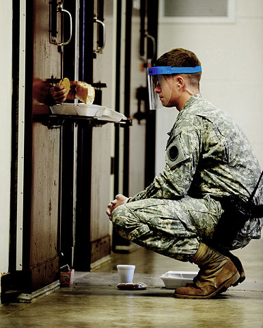 Guard delivers meal to solitary prisoner