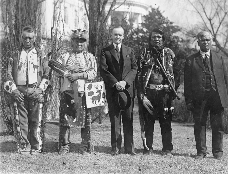 President Coolidge stands with Osage Native Americans after the ratification of the Indian Citizenship Act, 1924.